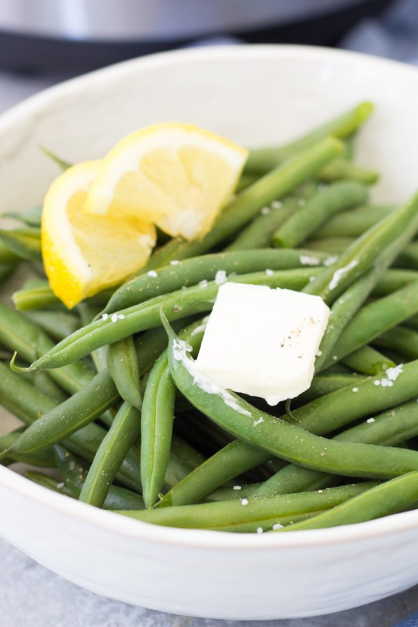 Green beans in a serving bowl with butter and lemon.
