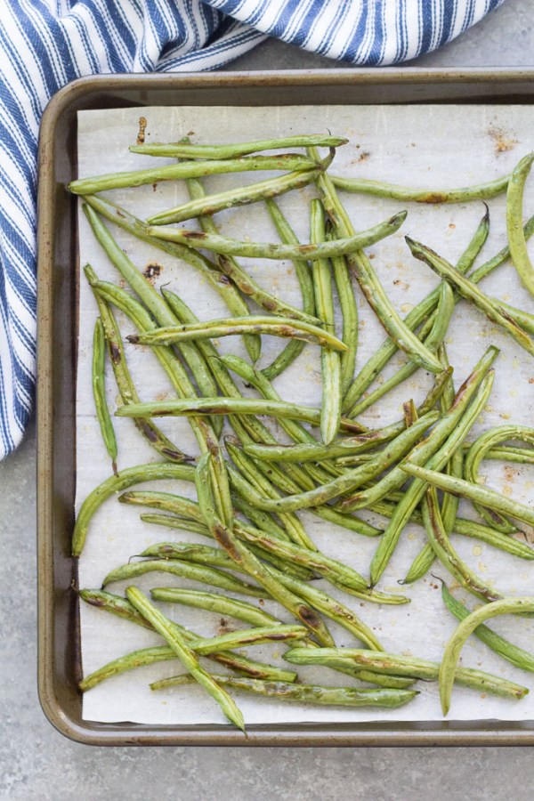 Top down view of baked green beans on a parchment paper-lined baking sheet.