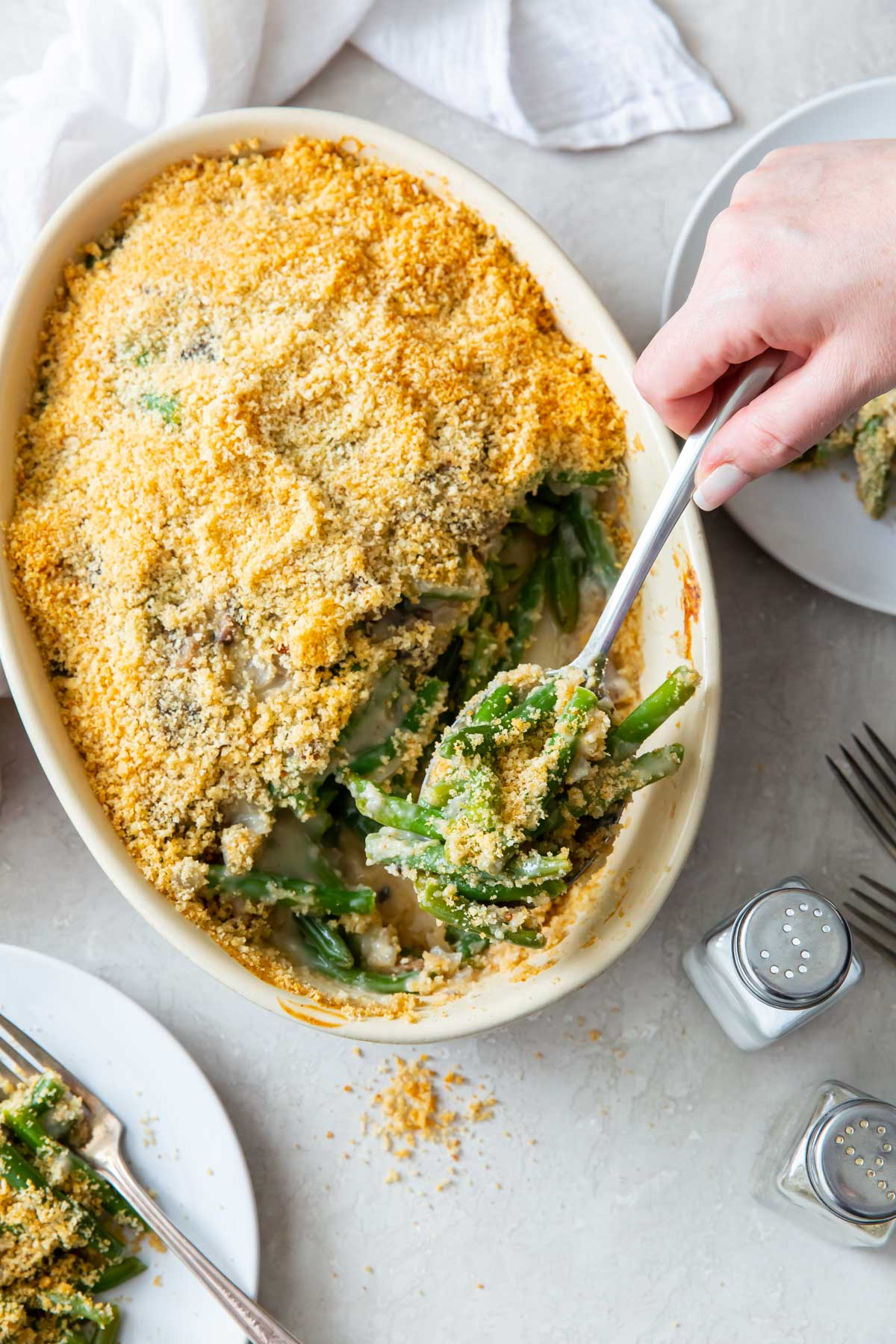 serving green bean casserole with spoon from baking dish