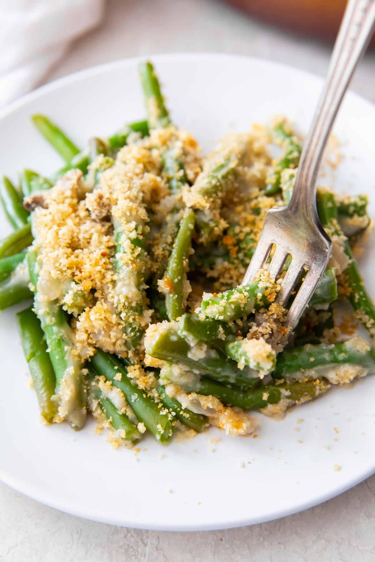 serving of green bean casserole recipe on a plate with a fork