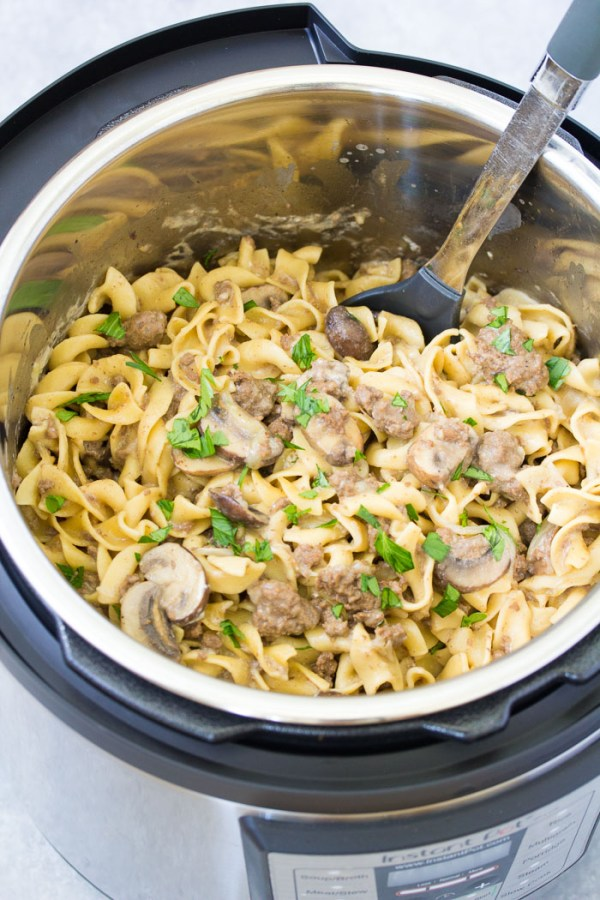 Easy beef stroganoff in an instant pot, with a serving spoon.