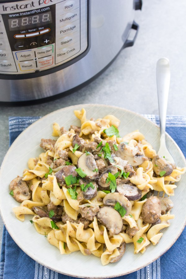 Healthy ground beef stroganoff with mushrooms on a plate, garnished with parsley.