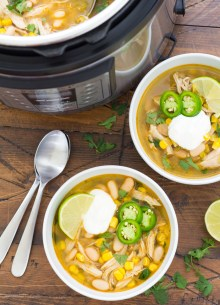 Two bowls of white chicken chili with toppings, next to an Instant Pot full of chili.