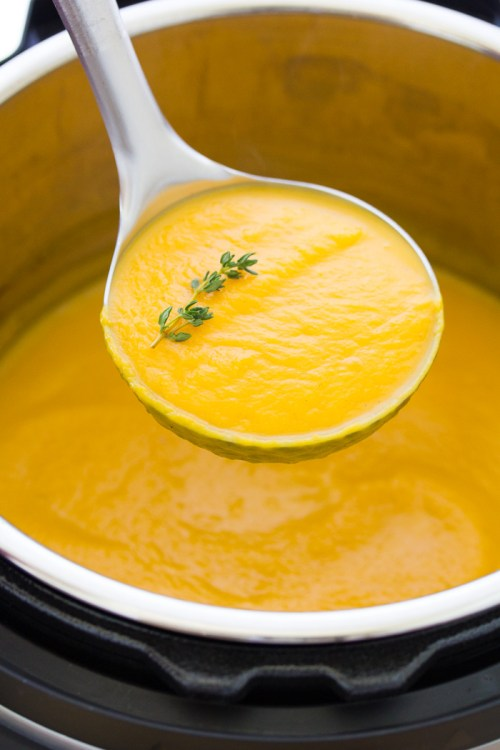Butternut squash soup in a ladle spoon over an Instant Pot full of soup.