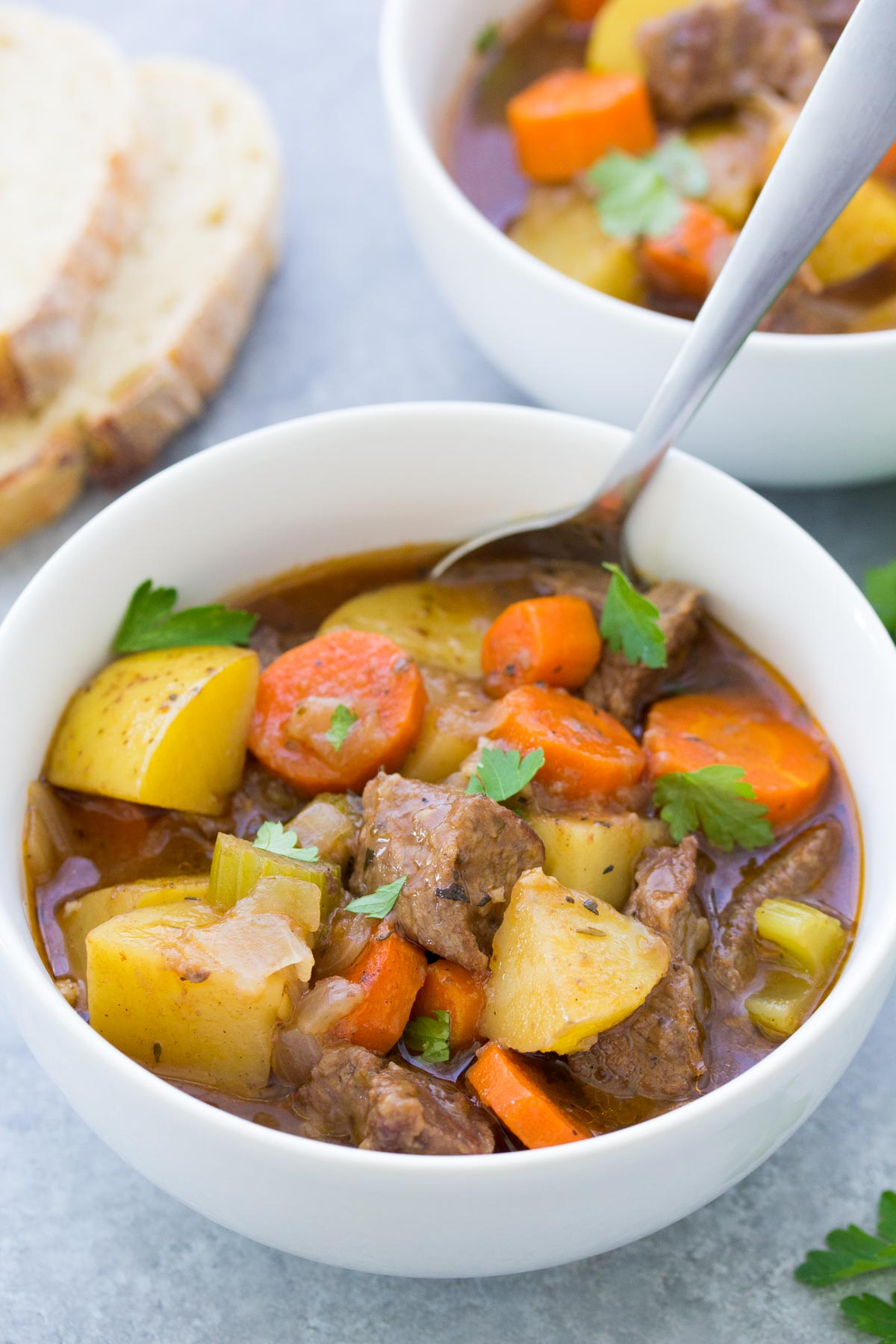 beef stew with potatoes and carrots in a white bowl with a spoon