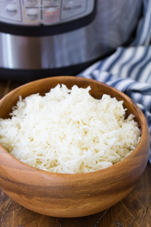 Cooked white rice in a wooden bowl, with an Instant Pot pressure cooker in the background.