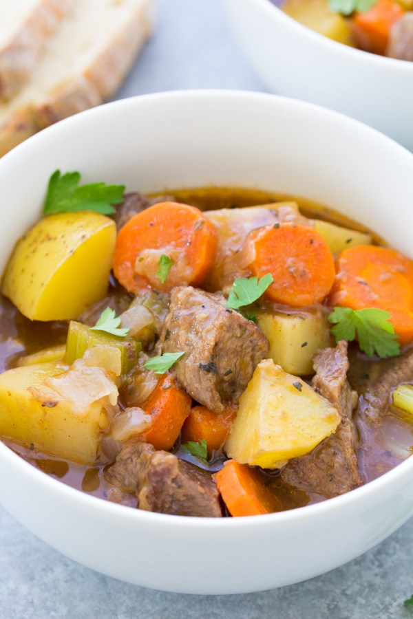 Close up of slow cooker beef stew in a white bowl.