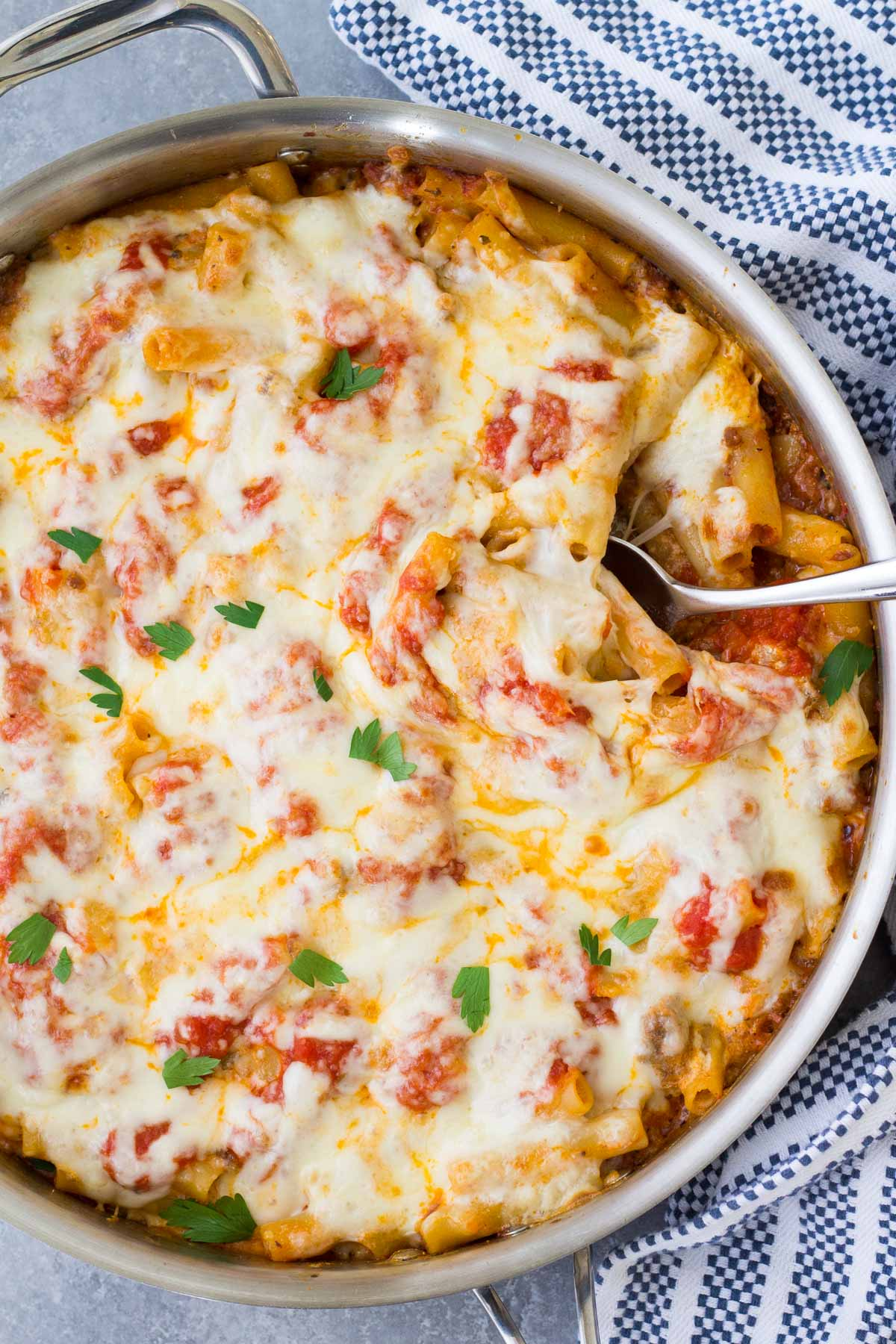 Baked ziti in a skillet with a serving spoon.
