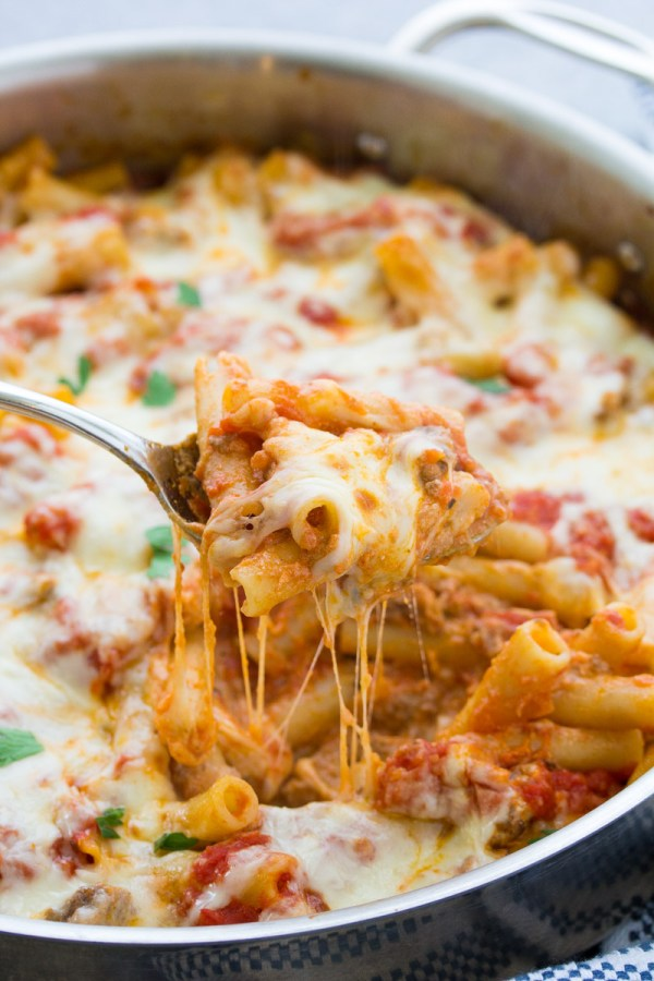 Close up of cheesy baked ziti pasta on a serving spoon, over a skillet.