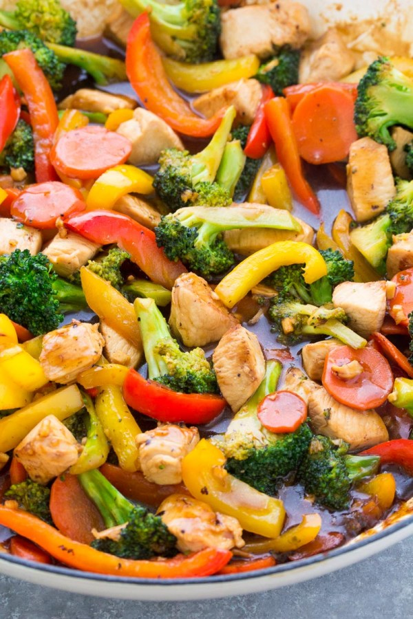 Close up of chicken and broccoli stir fry with carrots and bell peppers.