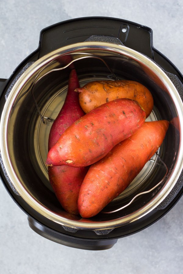 Sweet potatoes on a metal trivet in an instant pot before pressure cooking.