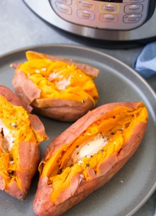 Baked sweet potatoes with butter, salt and pepper on a plate in front of an instant pot.