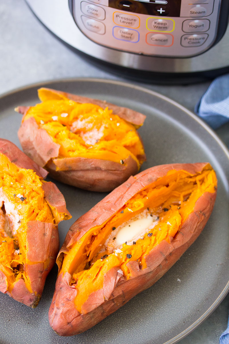 pressure cooked sweet potatoes with butter, salt and pepper on a plate in front of an instant pot.