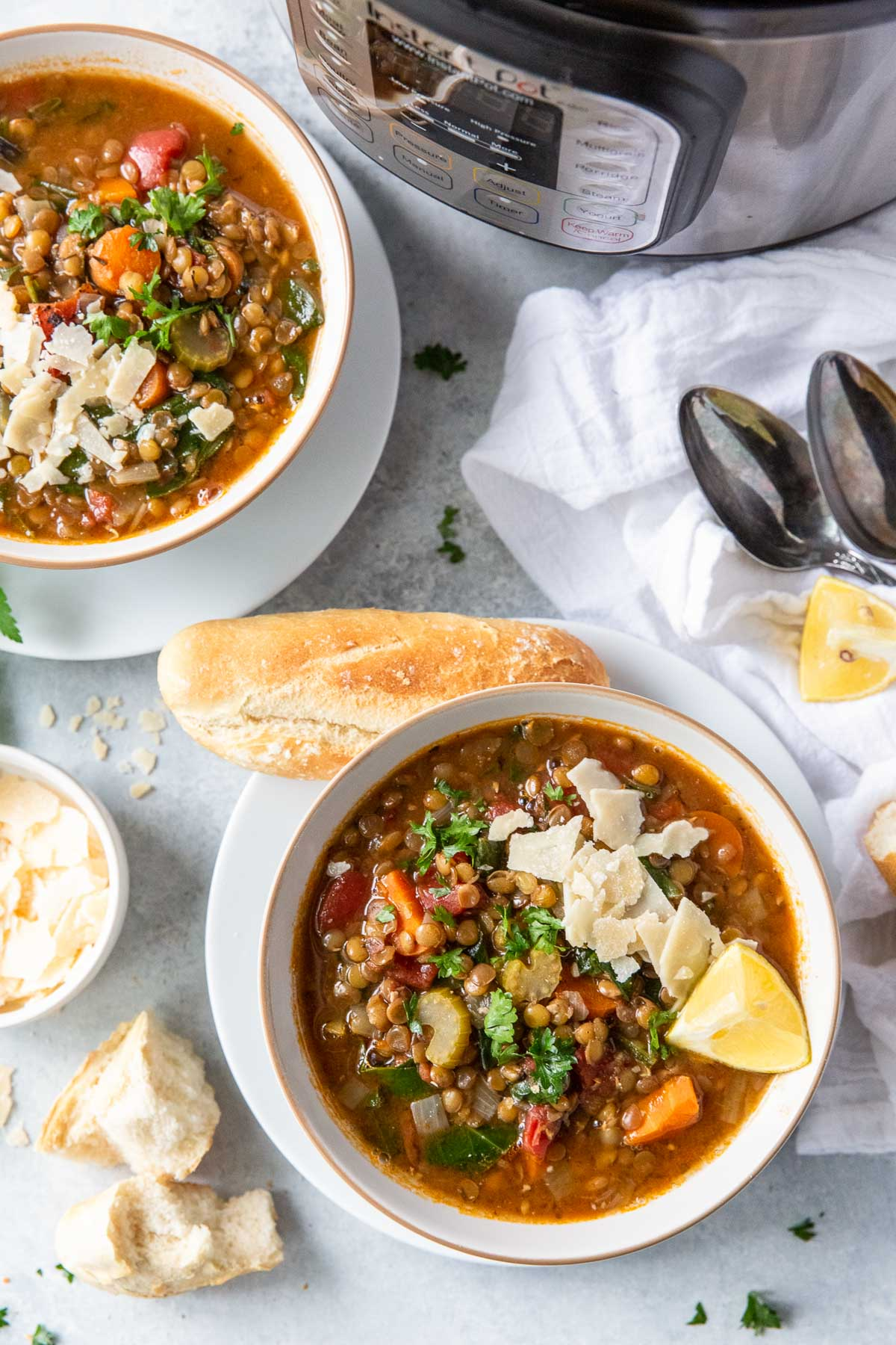two bowls of instant pot lentil soup served with parmesan, lemon and french bread