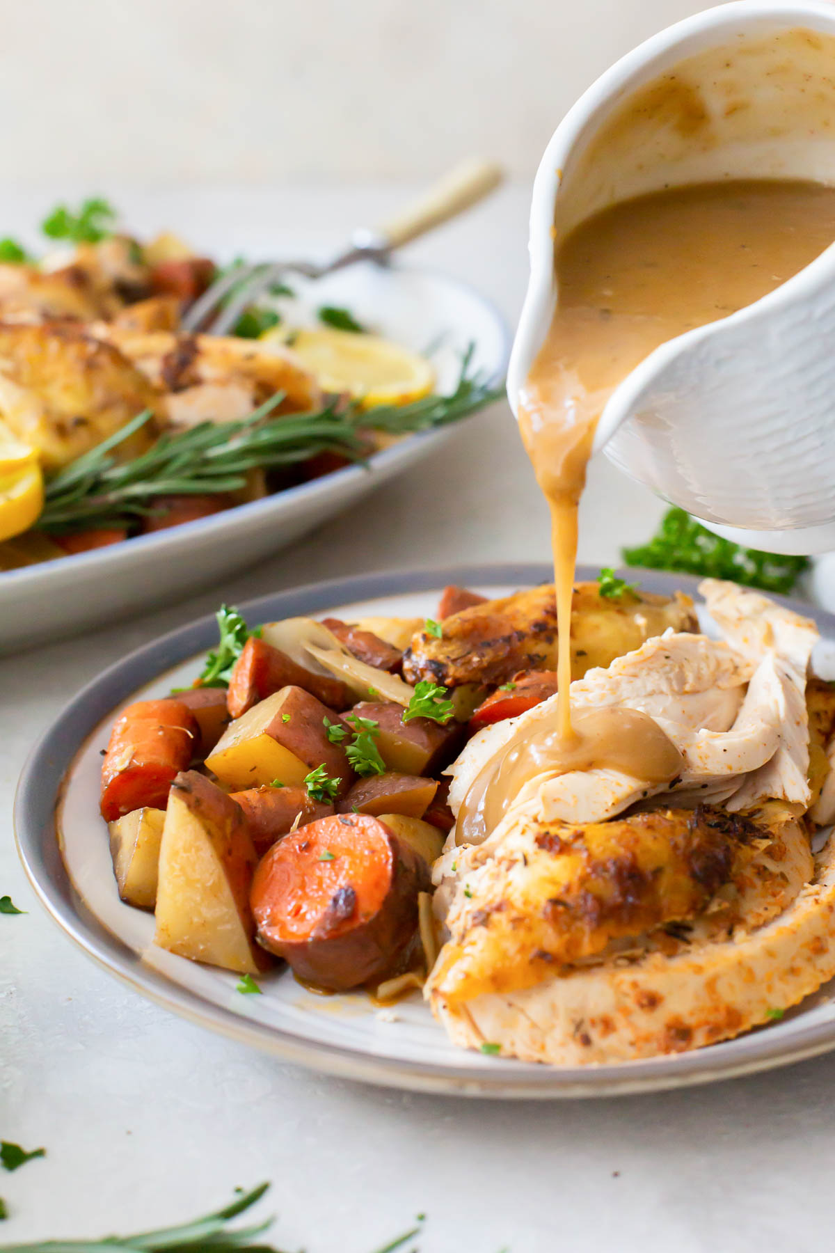 pouring gravy onto chicken on a plate with vegetables