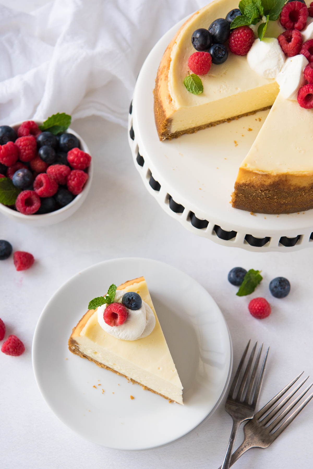 slice of cheesecake on a plate with whole cut cheesecake in background