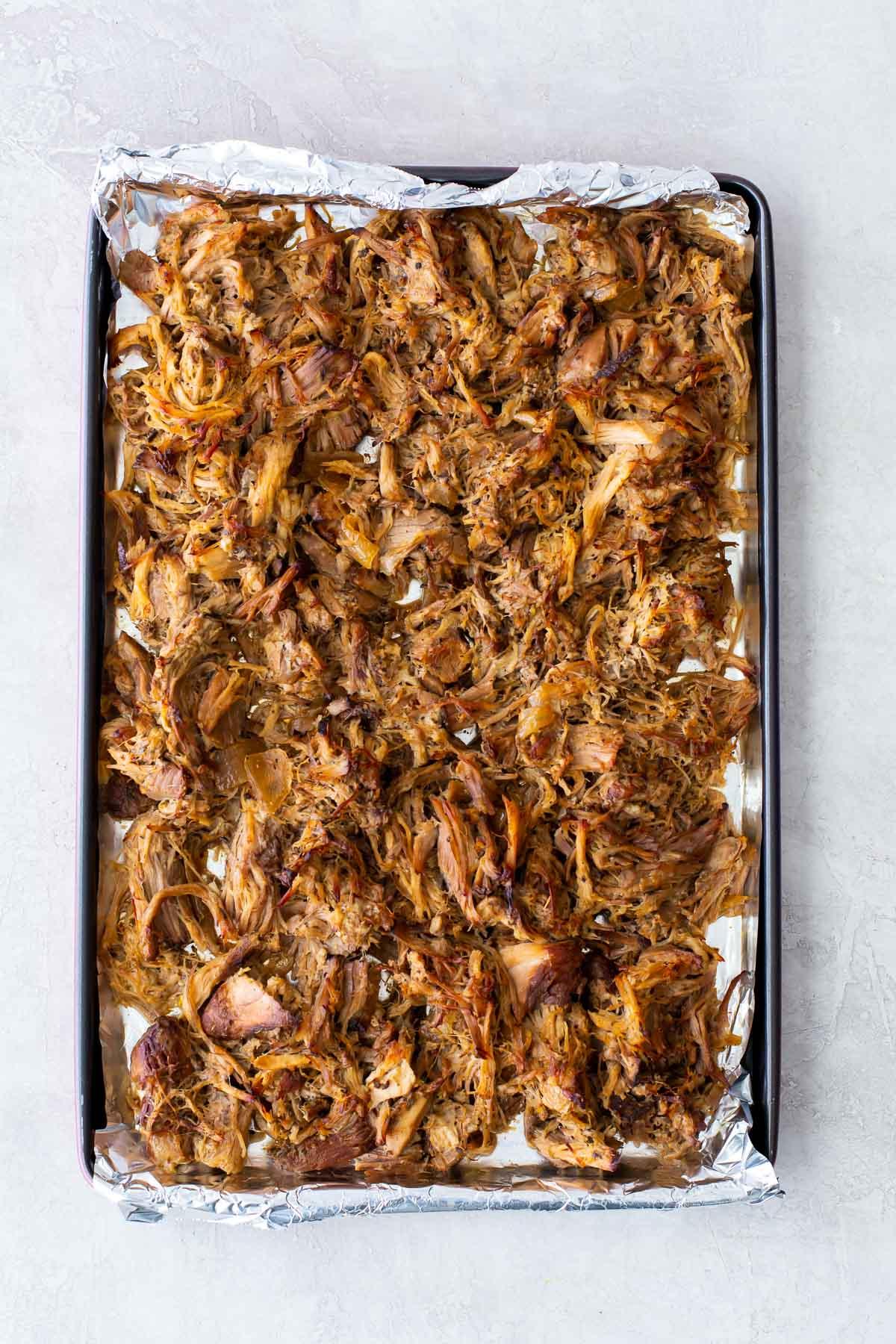 shredded pork carnitas on a foil lined sheet pan
