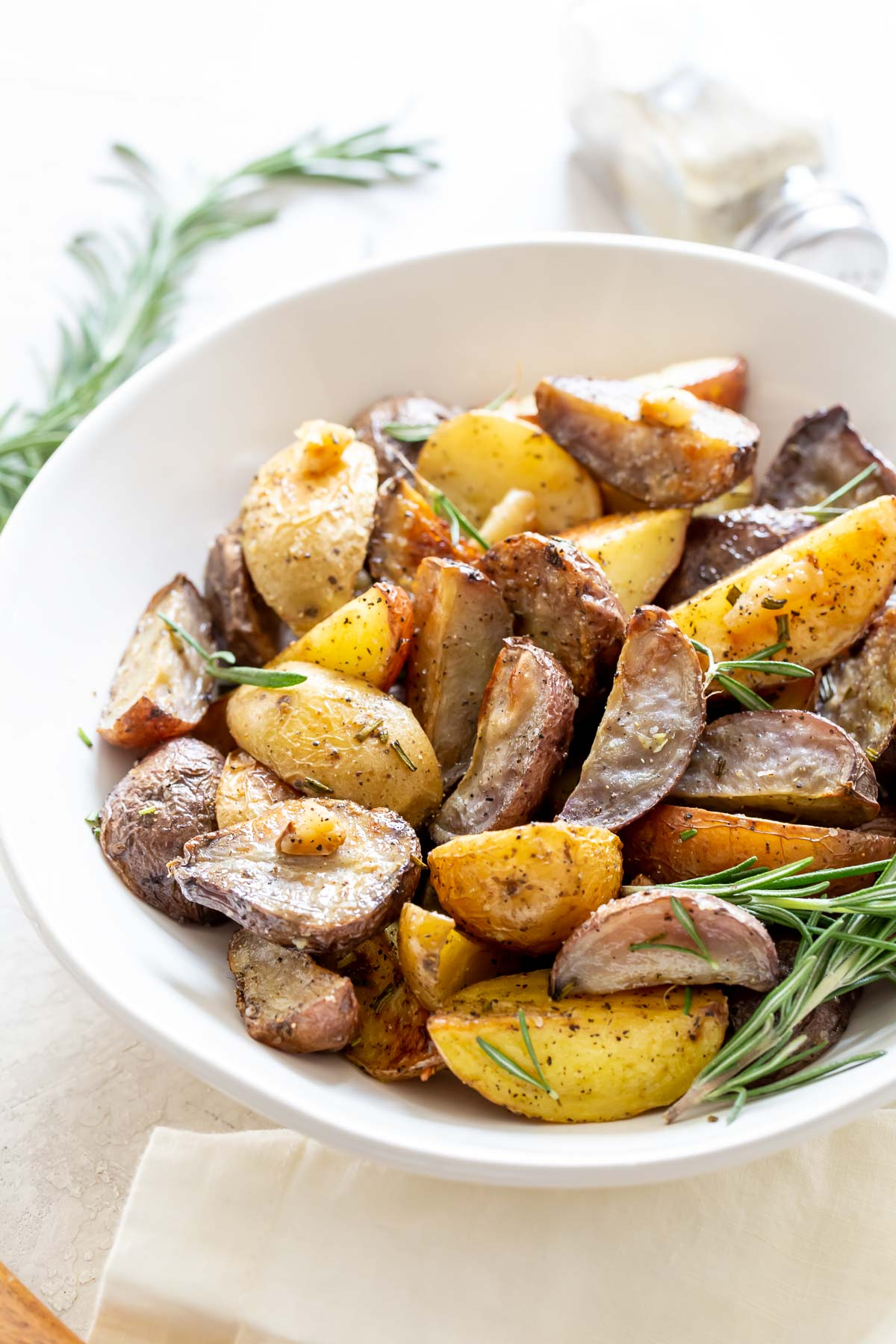 garlic rosemary roasted potatoes in white serving bowl