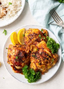 three air fryer chicken thighs on a plate with lemon and parsley garnish