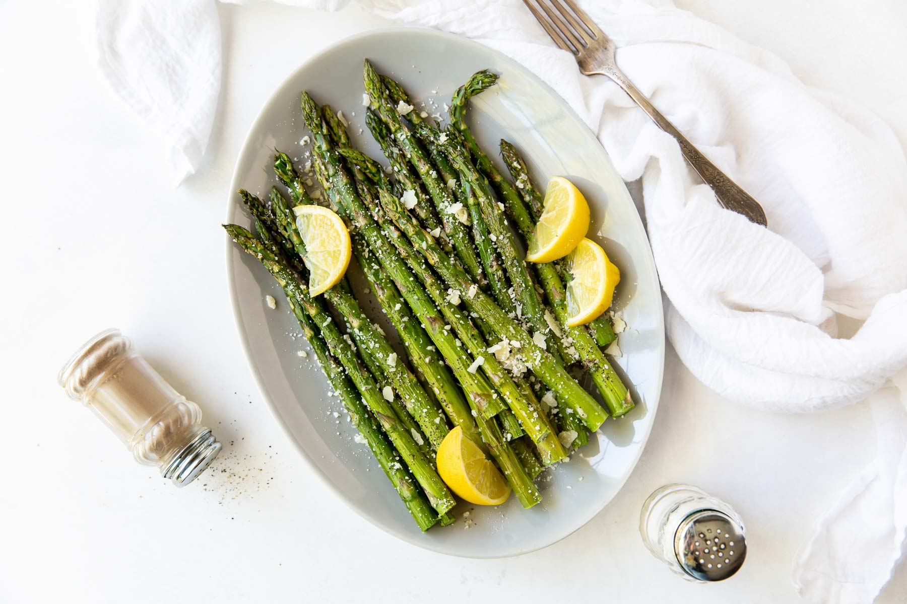 asparagus on white serving plate with lemon and parmesan
