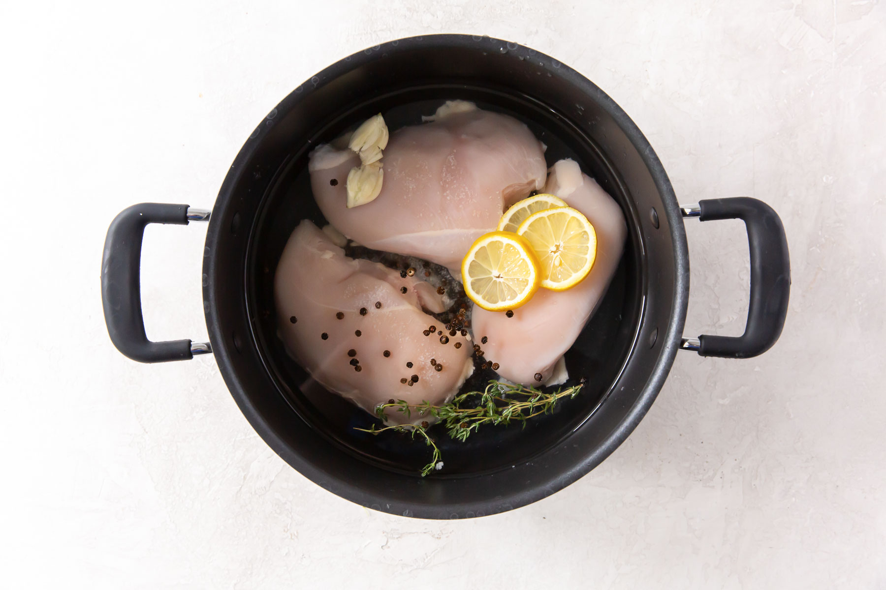 raw chicken, water, lemon, garlic, thyme and peppercorns in pot