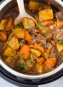 beef stew in an instant pot with a wooden spoon