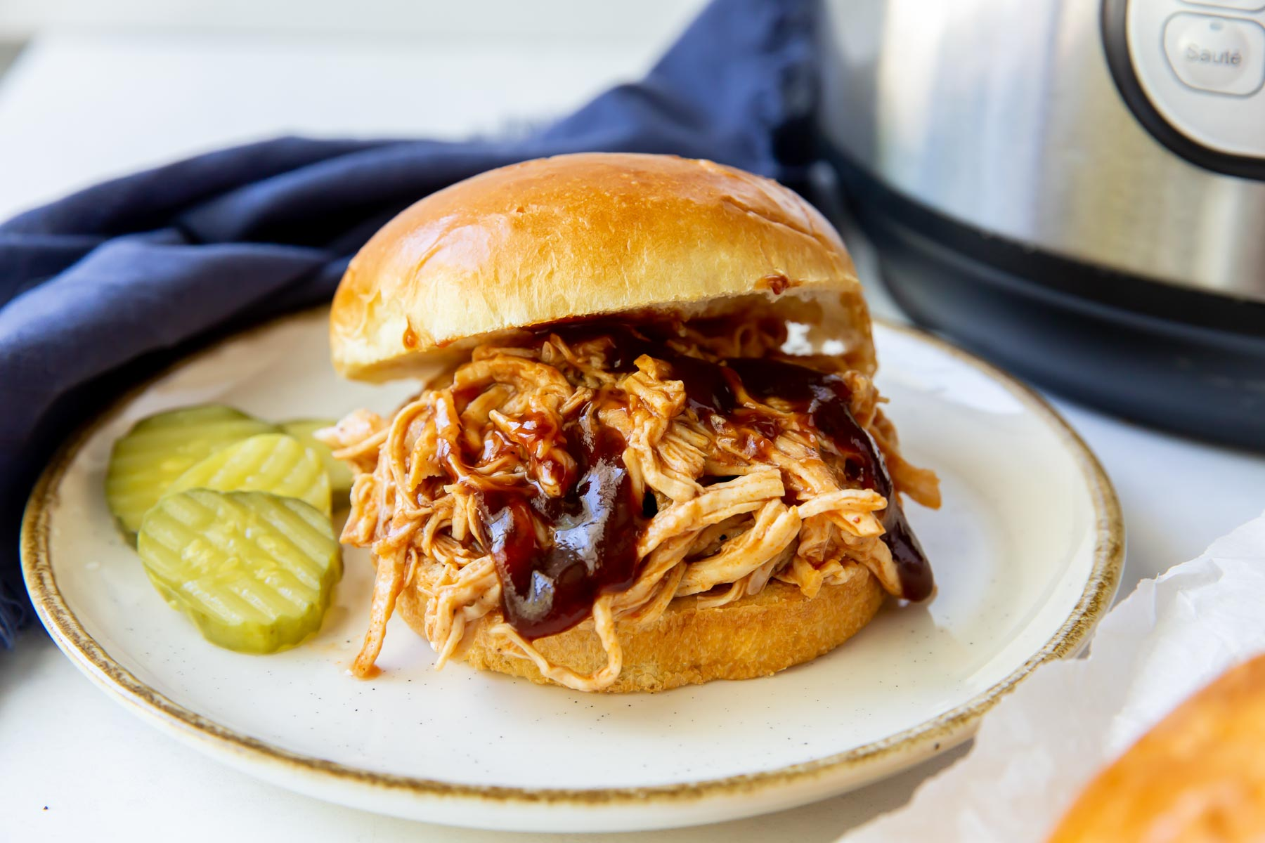 pulled chicken served on burger bun with bbq sauce and pickles on the side