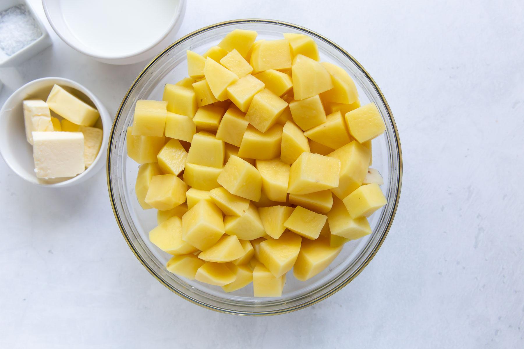 recipe ingredients: chopped yukon gold potatoes, butter, milk and salt in bowls