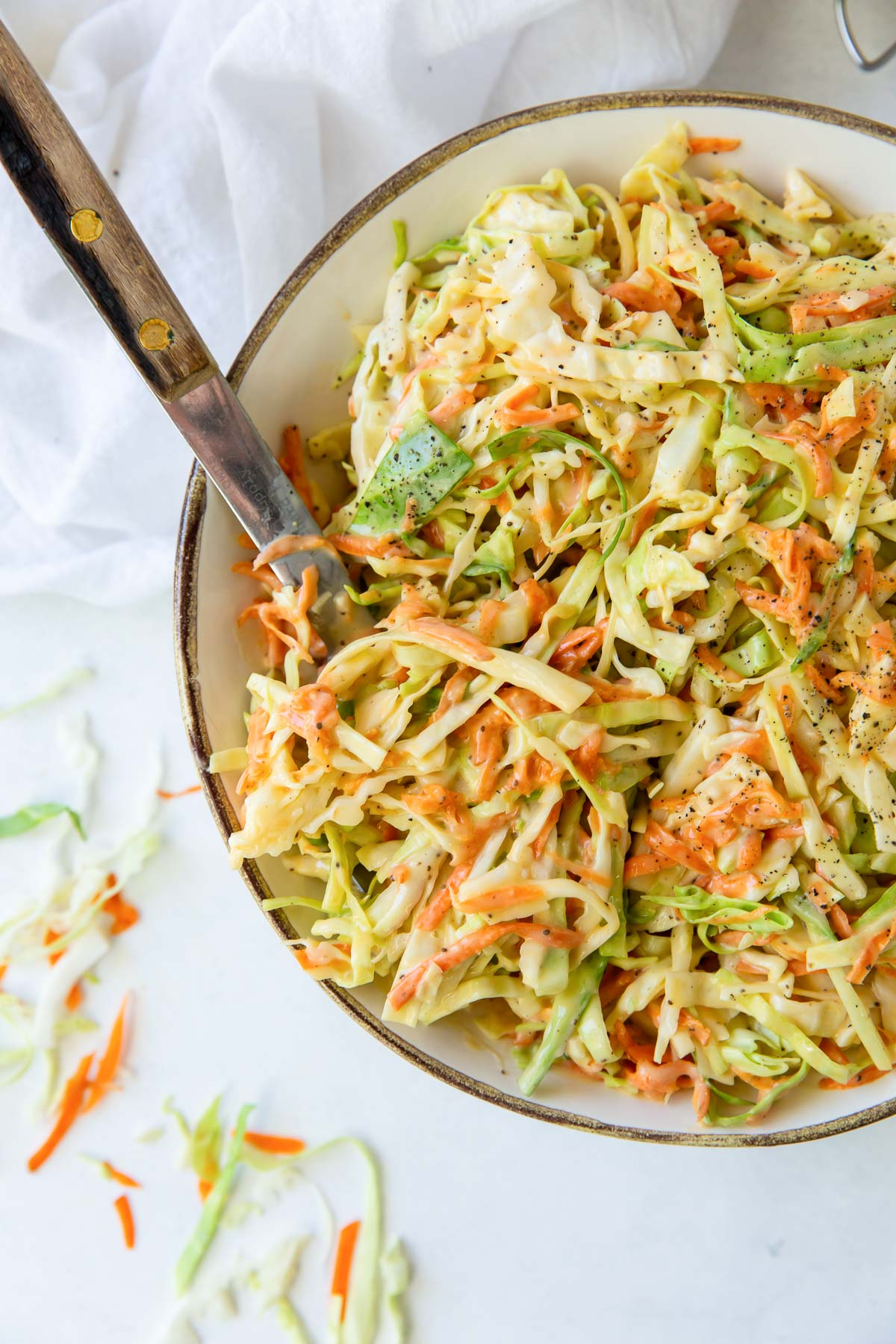 cabbage and carrot coleslaw in a bowl with a serving spoon