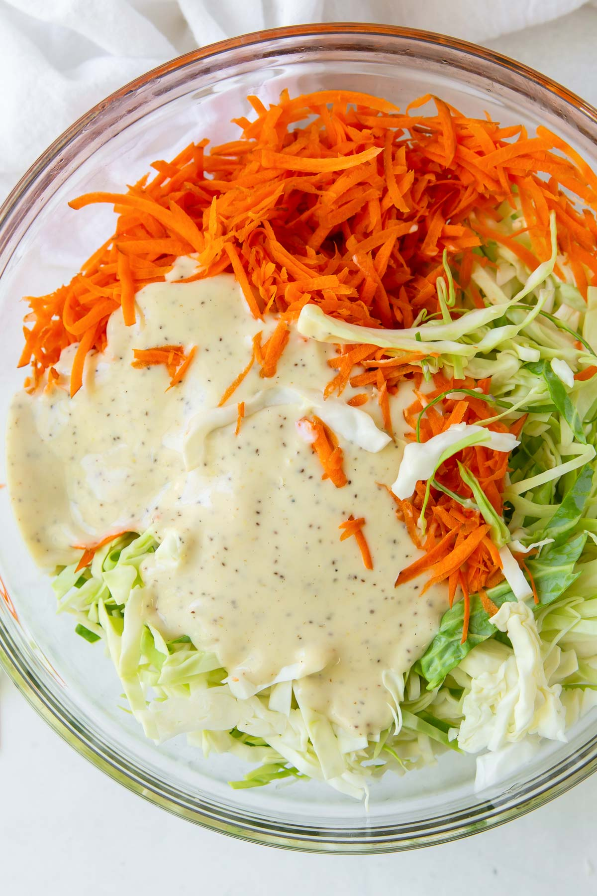 coleslaw dressing poured onto shredded cabbage and carrot