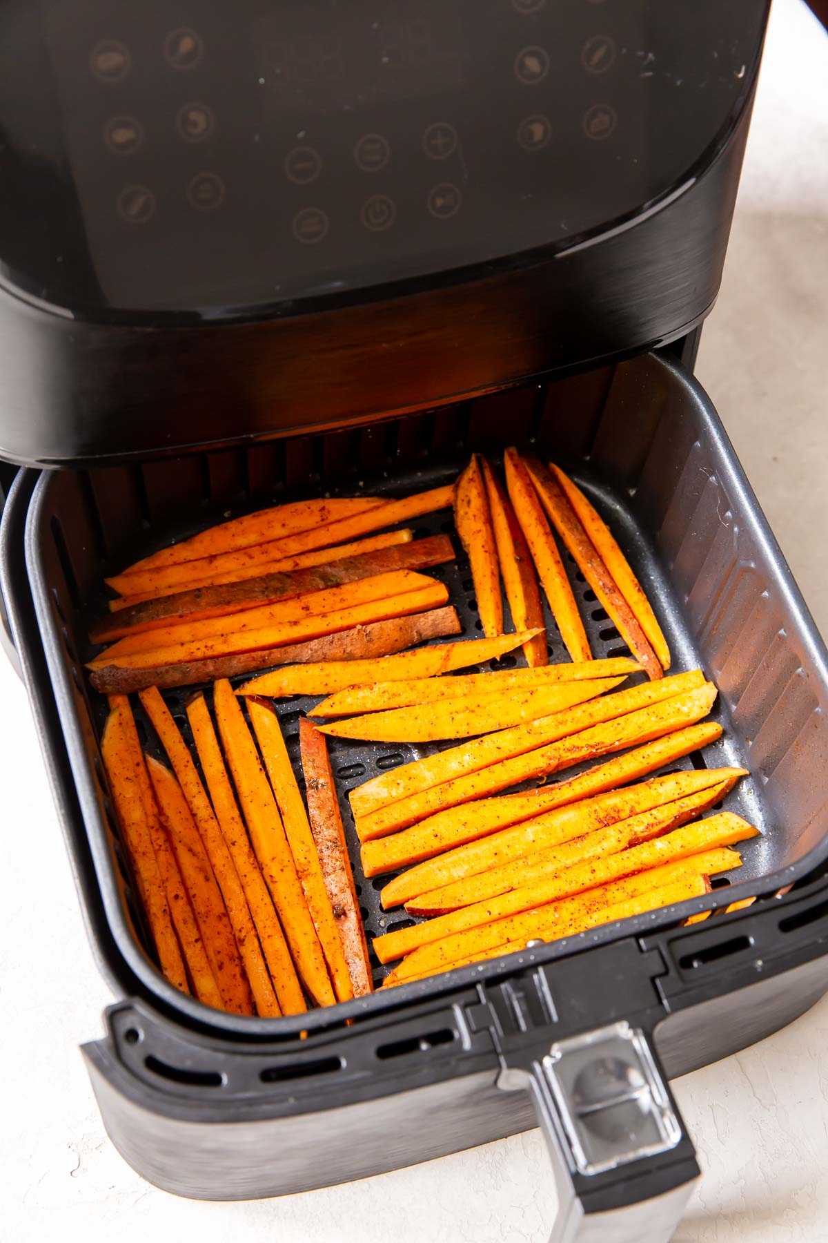 uncooked sweet potato fries in a single layer in air fryer