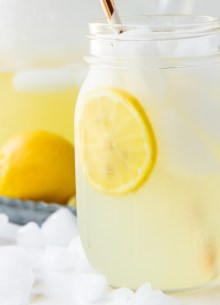 glass of homemade lemonade with ice, lemon slices and a straw