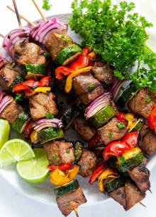 steak and vegetable kabobs stacked on a plate with lime and parsley