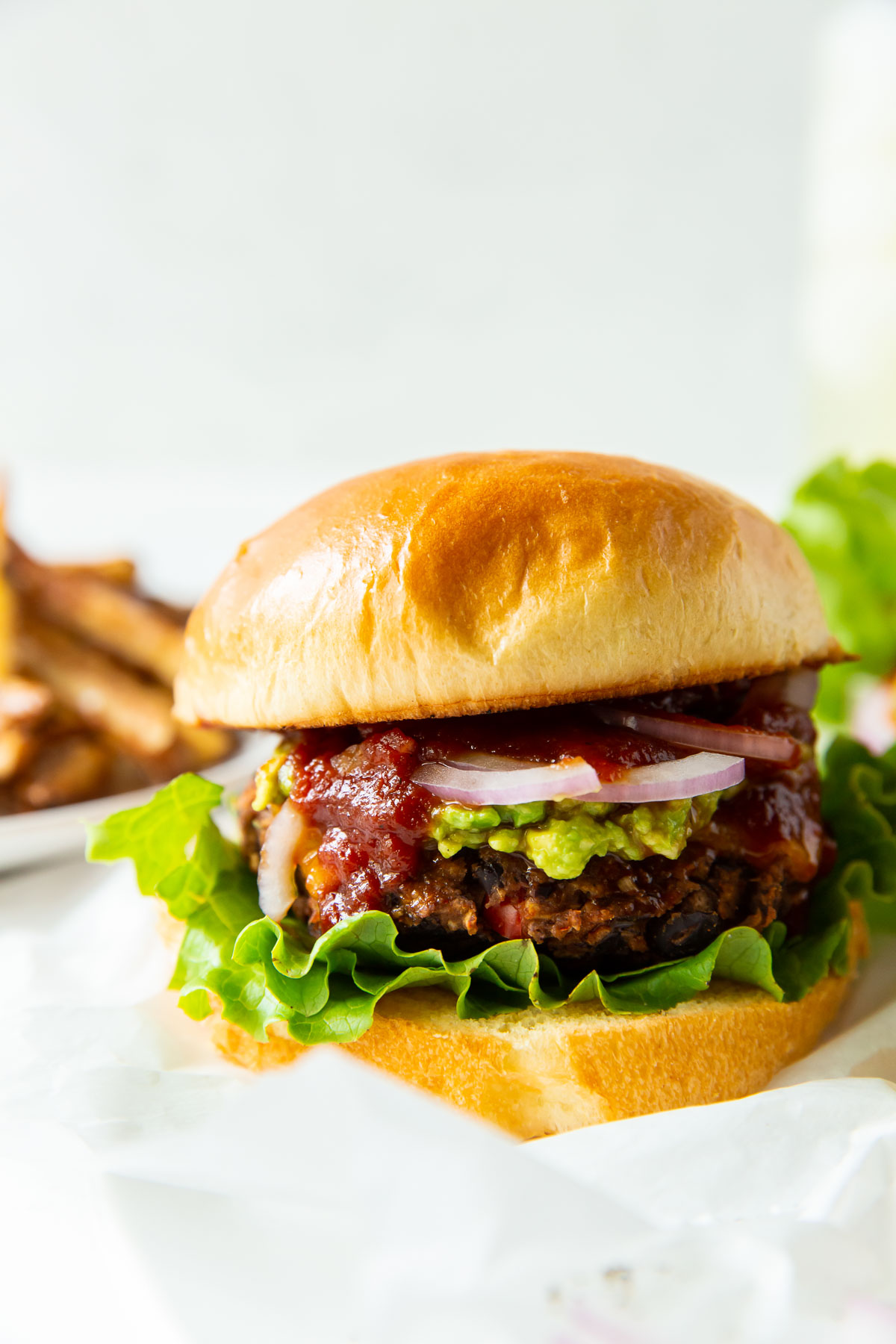 black bean burger served on a bun with bbq sauce, lettuce and red onion