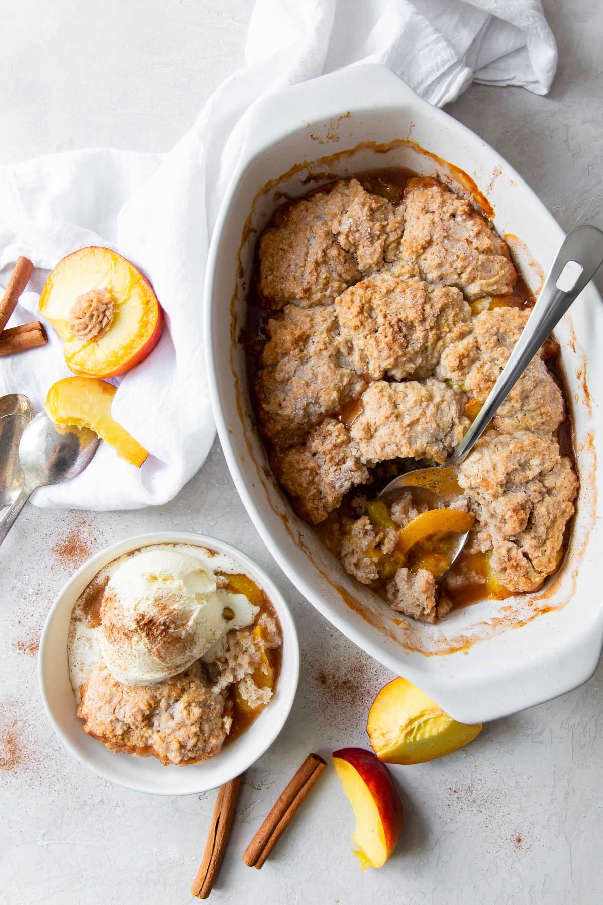 baked peach cobbler in a dish and a serving of cobbler in a small bowl topped with vanilla ice cream