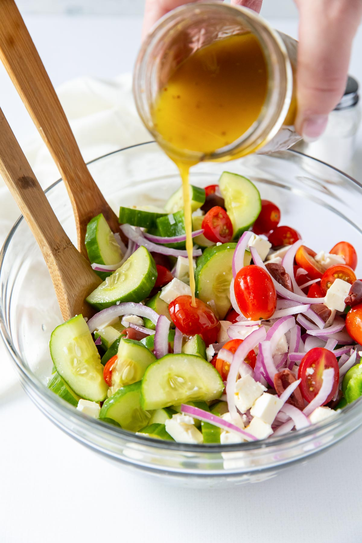 pouring greek salad dressing onto salad in a bowl