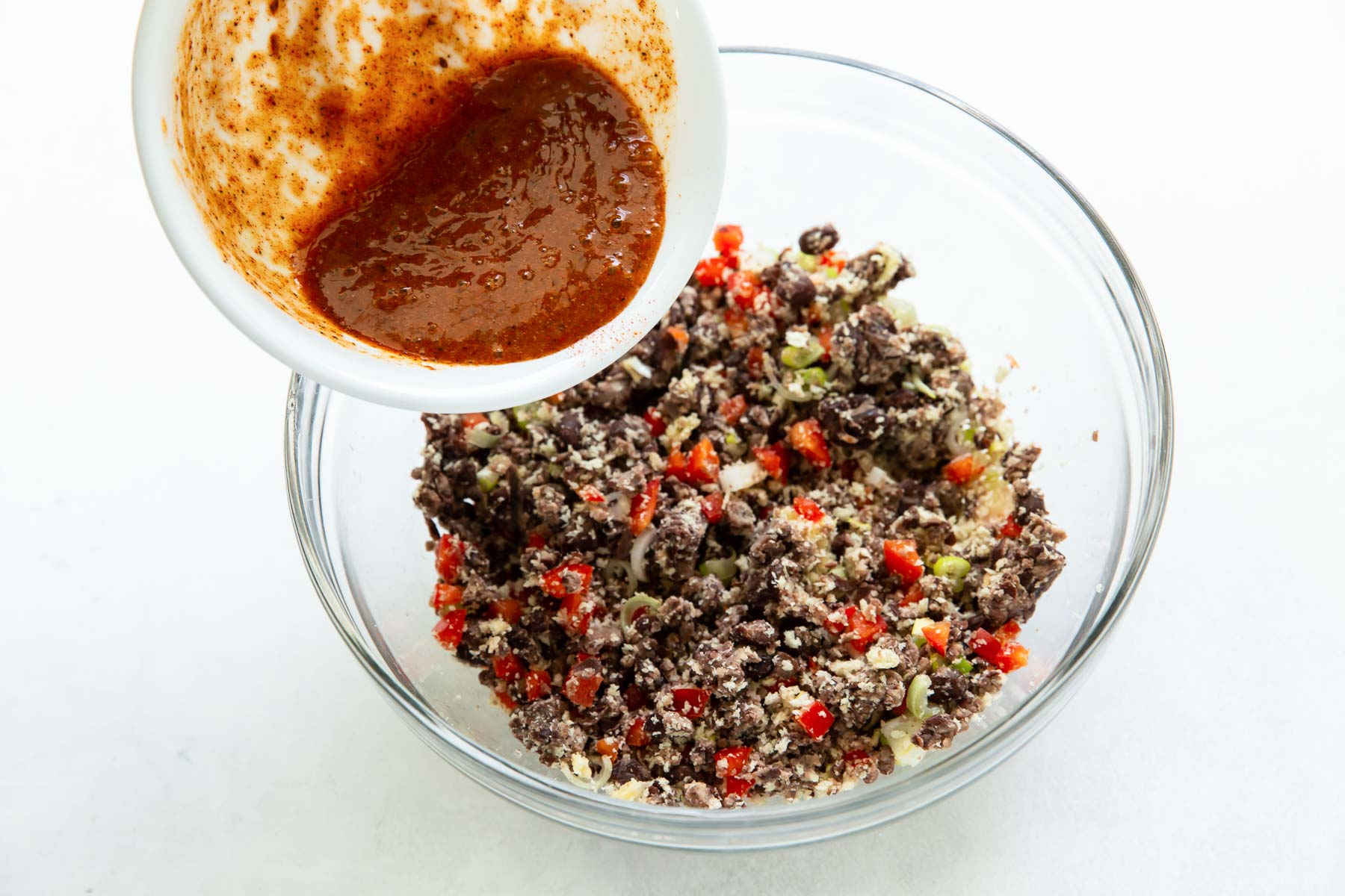 pouring egg and seasoning mixture into black bean mixture