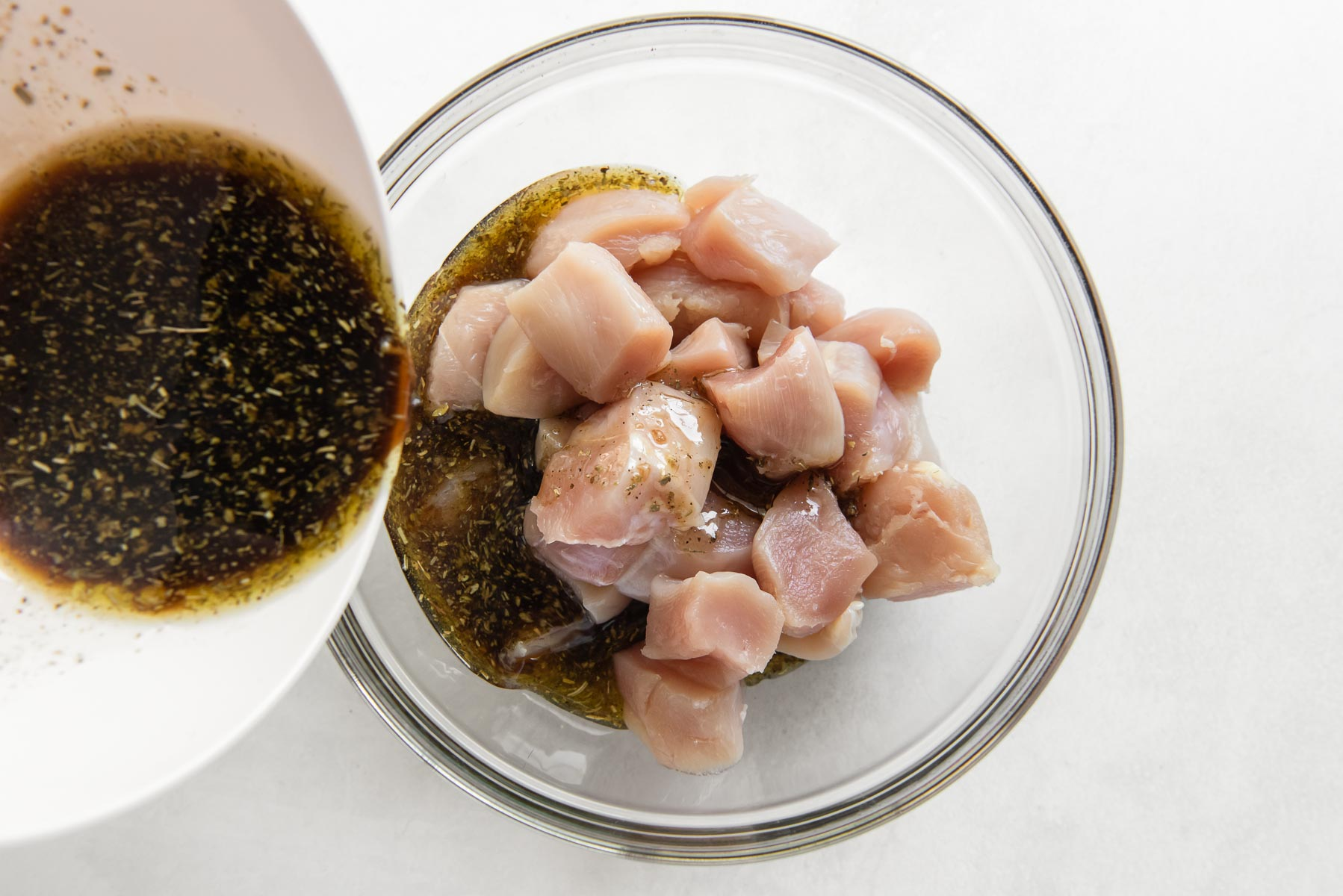 pouring marinade onto chicken pieces in bowl