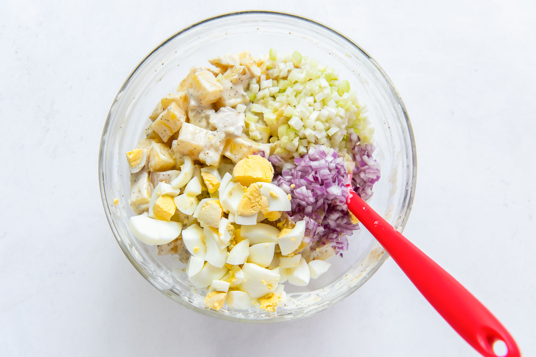 stirring hard boiled eggs, celery and red onion into salad