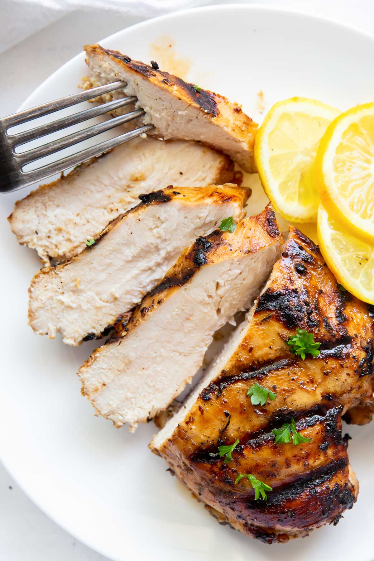 partially sliced chicken breast on a plate with a fork and lemon slices
