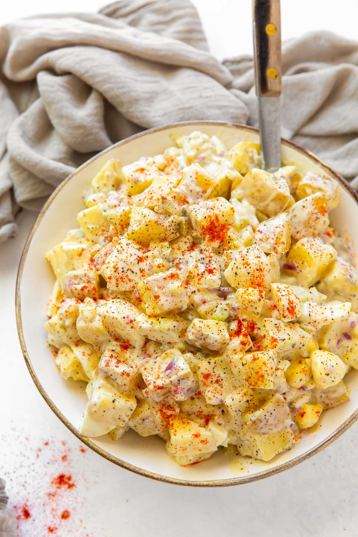 potato salad in a serving bowl with a serving spoon