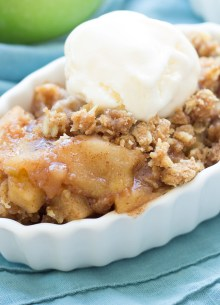 slow cooker apple crisp served in a small white dish with a scoop of vanilla ice cream
