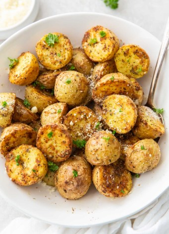 air fryer potatoes with parmesan in a white bowl with serving spoon