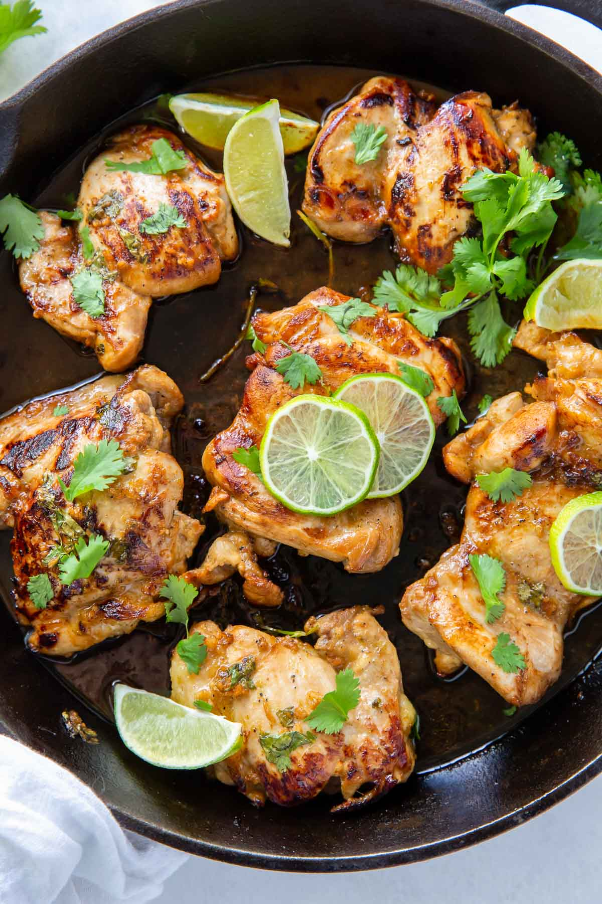 cooked chicken thighs in a cast iron skillet with cilantro and lime slices