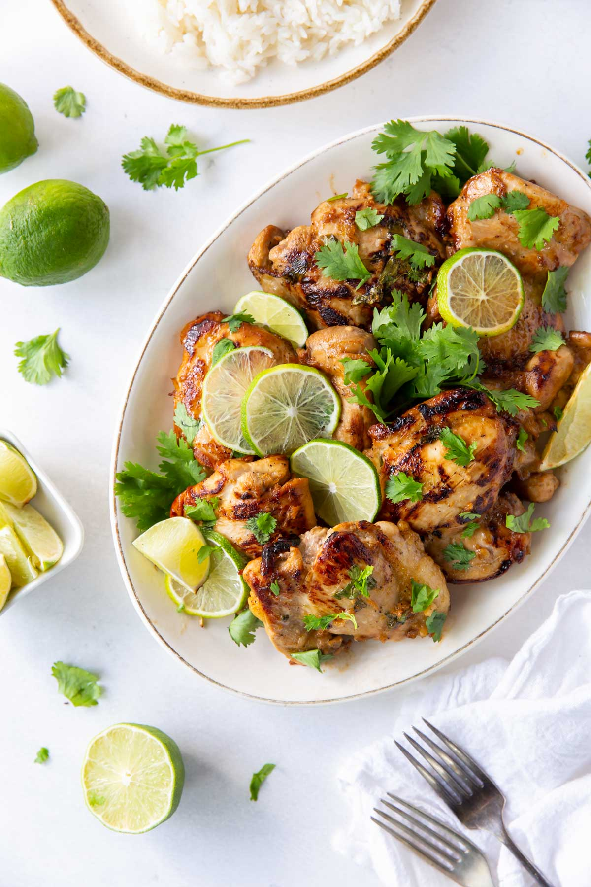 chicken thighs with cilantro and lime on a serving platter with white rice in background