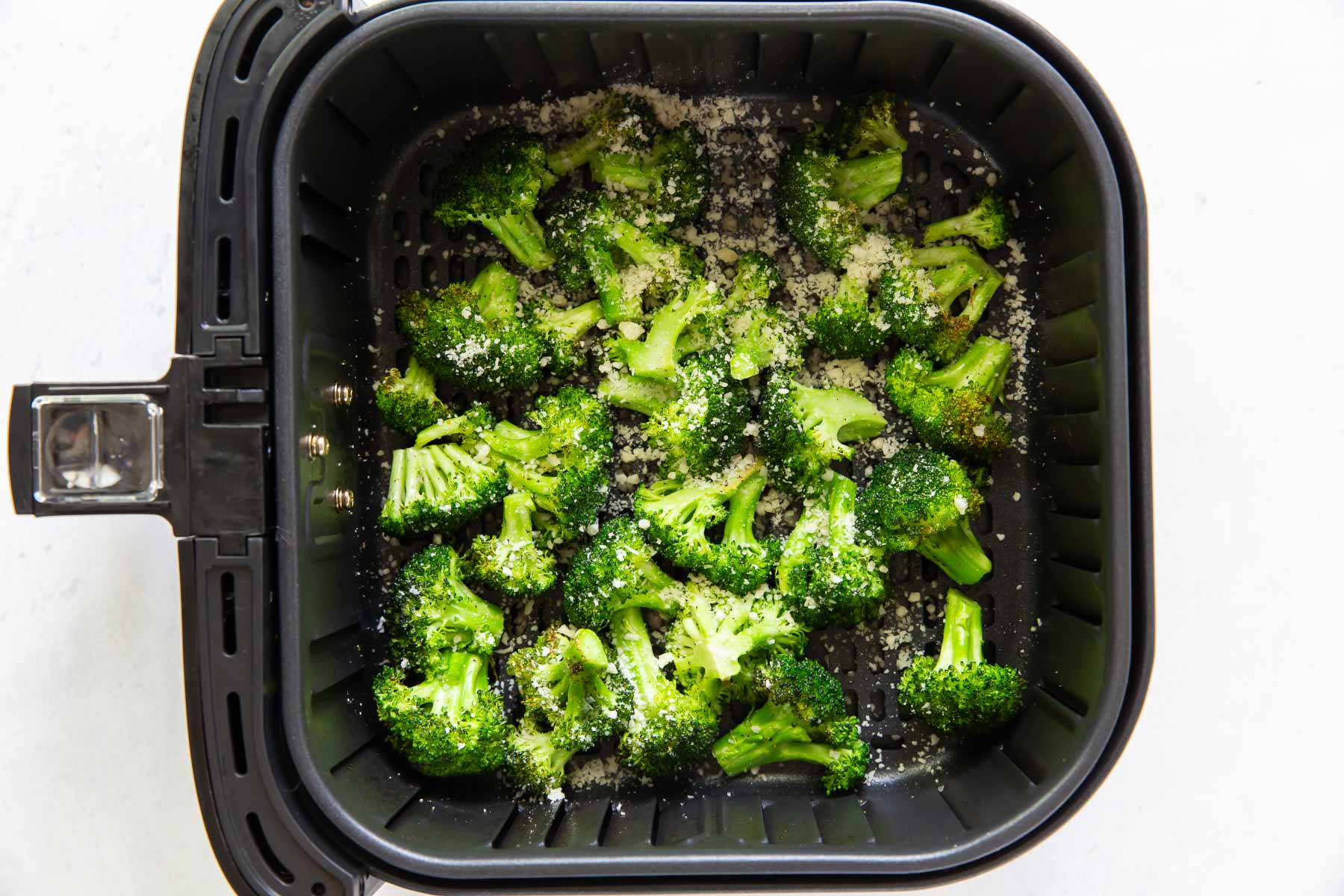 parmesan cheese added to broccoli in air fryer basket