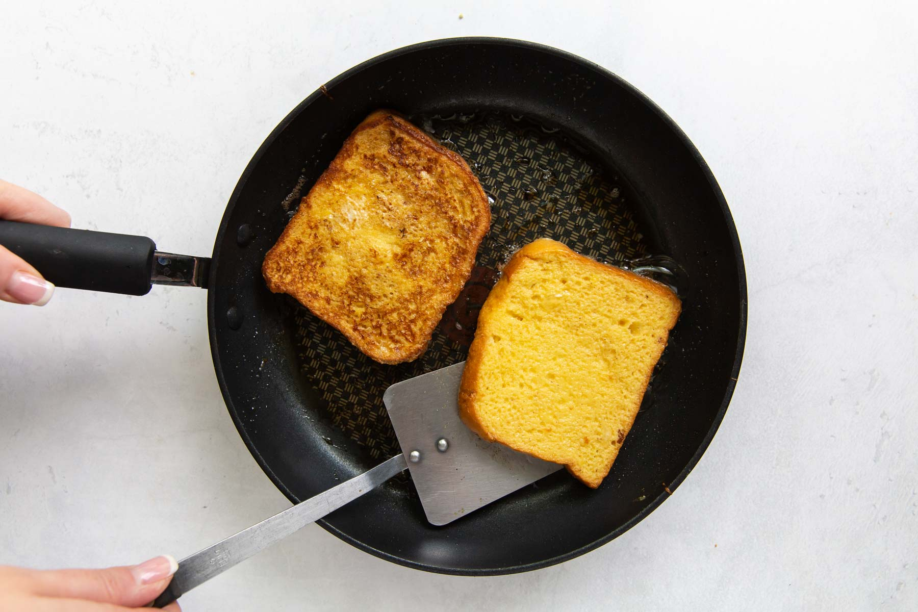 two pieces of french toast cooking in a skillet, with a spatula flipping one piece