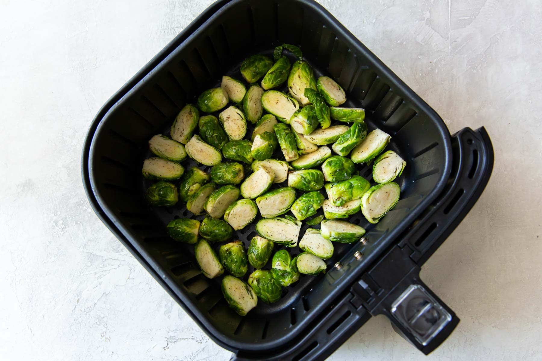 uncooked brussels sprouts in air fryer basket