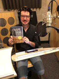 Actor Rob Doyle holding his copy of Carpe Diem, Illinois