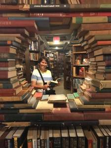 Kristin looking through a tunnel of books at The Last Bookstore